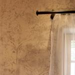 Tonputzwand von Emoton mit floralem Muster und Gardine